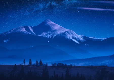 Distant mountain top covered with snow at night. Milky way in a starry sky.