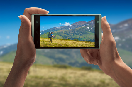 Girl take a picture of hiker with backpack in a mountain valley on smartphone. Travel concept. 版權商用圖片