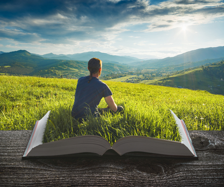 Man in a grass enjoy the valley on the pages of an open magical book. Majestic landscape. Travel and education concept.