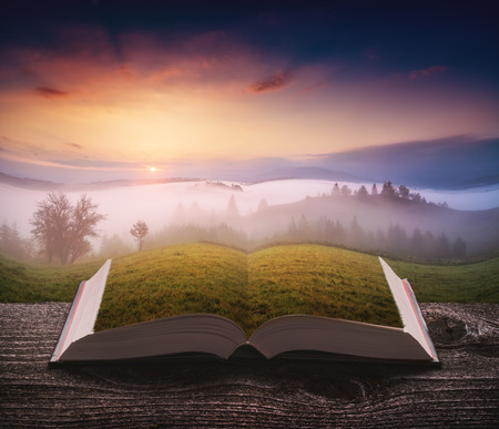Majestic spring scene of sunrise in a alpine valley on the pages of an open magical book. Majestic landscape. Travel and education concept.