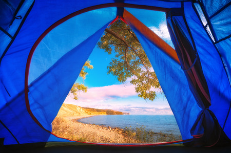 View from camping tent to the sea beach. Travel and vacation concept.