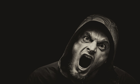 Angry scarry shouting man in a hood on a dark background with place for text. Vintage sepia stylization.