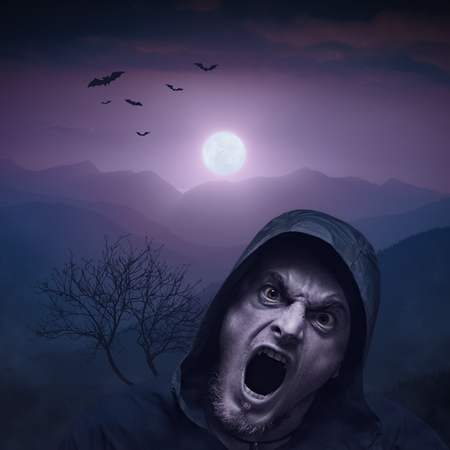 Angry vampire man at night in a light of rising moon.