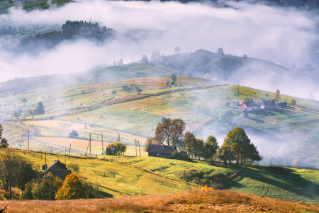 Beautiful countryside view of alpine carpathian village covered with deep fog. Grassy hills and meadows illuminated by morning sunlight. Wonderful nature scenery of Carpathians. 版權商用圖片 - 121116464