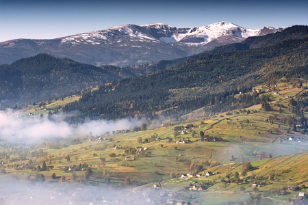 Beautiful countryside view of alpine carpathian village. Grassy hills and meadows illuminated by morning sun. Wonderful nature scenery of Carpathians. Banque d'images - 121116488