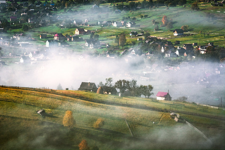 Beautiful countryside view of alpine carpathian village covered with fog. Grassy hills and meadows illuminated by morning sunlight. Wonderful nature scenery of Carpathians. Banque d'images - 121116494