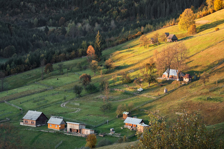 Beautiful countryside view of alpine carpathian village. Grassy hills and meadows illuminated by evening sunlight. Life on a top. Wonderful nature scenery of Carpathians.