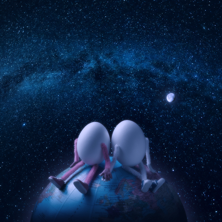 Couple of egg humans sitting on a Earth planet in outer space under the starry sky.
