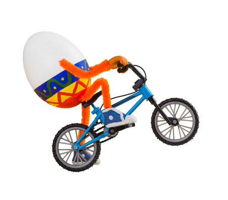 Easter egg on a miniature bike isolated on white background.