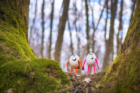 Couple of Easter egg hikers walking in a fairytale spring forest. Travel and holiday concept. Banque d'images - 121116532