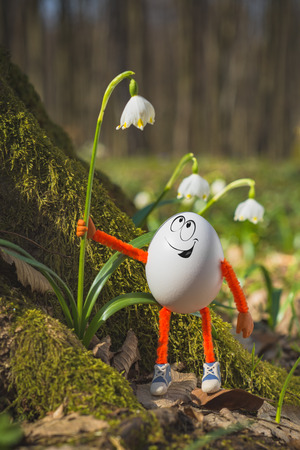 Happy Easter egg hold a white flower in a spring forest. Holiday concept.