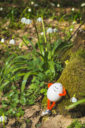 Happy Easter egg enjoy the sunlight in a spring forest. Travel and nature concept. Imagens