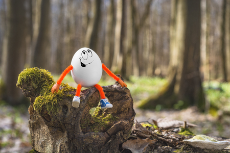 Happy Easter egg sitting on a mossy stump in a spring forest. Travel and nature concept. Imagens
