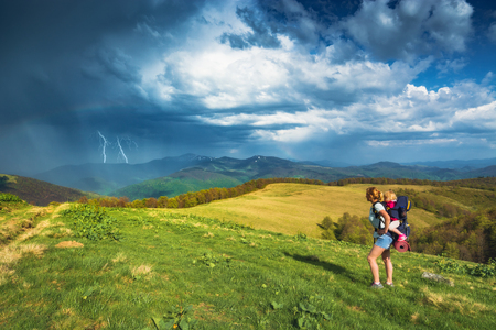 Active family. Mother hiker with her baby in a carrying for a child on a trekking day in mountains. The dramatic stormy rain clounds with lightning on horizon. Travel and family concept.