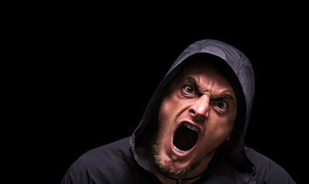 Angry scarry shouting man in a hood on a black background. Banque d'images - 121116564