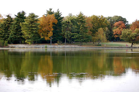 Lake reflecting Autumn colored trees. Stock Photo