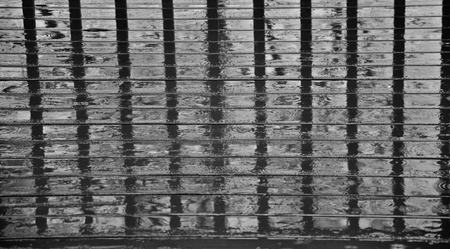 Deck rails reflected upon a wet deck in B&W. Stock Photo