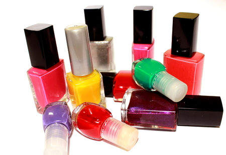 Colored nail polishes in white background Фото со стока