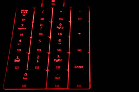 Computer keyboard with red illuminated buttons. Close up. Stock Photo