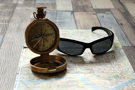 Compass and sunglasses lies on a map. Travelers equipment. Compass lying on the contrary.