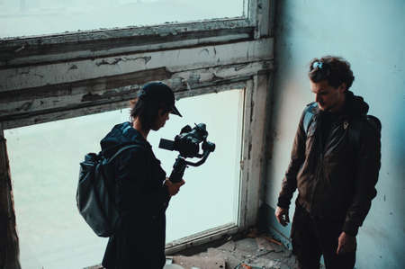 Long haired operator filming curly guy in destroyed building at window