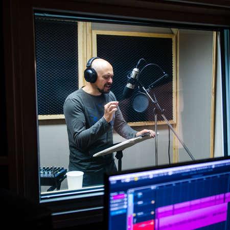 Bald man near microphone recording voice. Foto de archivo