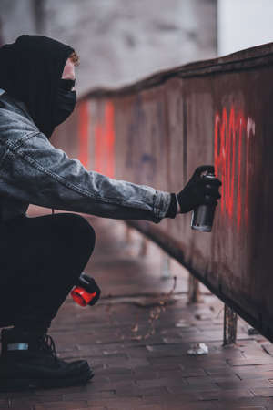 Using spray paint can to make protest sign. Charismatic man with hidden identity Stock Photo