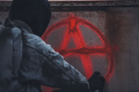 Back view of man in hood who paint anarchy symbol on the wall Stock Photo