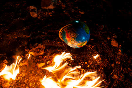 Close up of globe in fire at the floor of abandoned building. Allusion to a world of nowadays.