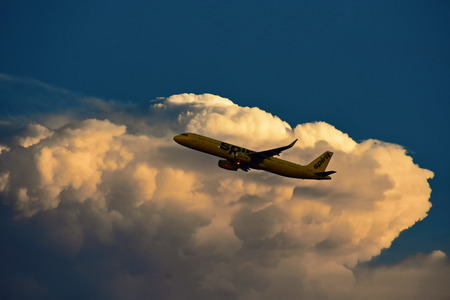 Orlando, Florida. September 25, 2018. Airplane from Spirit Airlines gaining altitude after takeoff, on beautiful sunset sky. Editorial