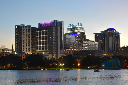 Orlando, Florida. October 17, 2018 Colorful illuminated buildings, green forest and swan boats in Eola Lake Park at Orlando Downtown.