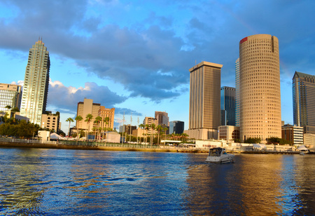 Tampa, Florida. October 06, 2018. Panoramic view Tampa Downtown and boat sailing on cloudy sunset background.