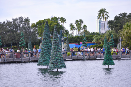 Orlando, Florida. October 19, 2018 People leaving the park and beautiful Christmas Tree over lake on cloudy sky background at Seaworld Theme Park.