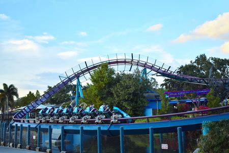 Orlando, Florida. November 19, 2018. People having fun rollercoaster ride on bluelight sky background in International Drive area.