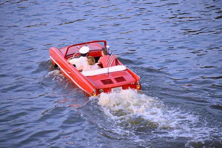 Orlando, Florida. November 15, 2018. Nice couple enjoying Amphibious red car ride over the blue lake at Lake Buena Vista area Editorial
