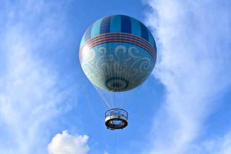Orlando, Florida; November 15, 2018 Air balloon flying on lightblue cloudy background at Lake Buena Vista
