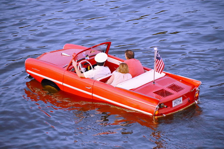 Orlando, Florida. November 14, 2018. Nice couple enjoying Amphibious red car ride over the blue lake at Lake Buena Vista area