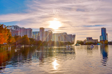 Orlando, Florida . December 24, 2018. Colorful buildings and autumn forest at Lake Eola Park on beautiful sunset background in Downtown Orlando (1)