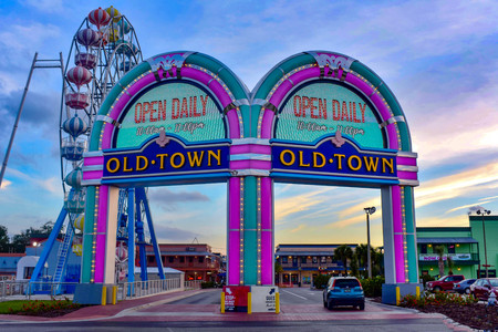 Orlando, Florida. December 28, 2018. Illuminated entrance arches and colorful big wheel at Kissimmee Old Town in 192 Highway area.