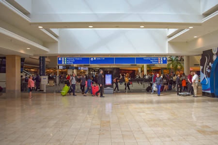 Orlando, Florida. March 01, 2019. People walking with baggage to different terminals and top view of Ticketing and check-in blue sign at Orlando International Airport.