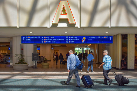 Orlando, Florida. March 01, 2019. People walking with baggage at Terminal A area in Orlando International Airport (5) Editorial