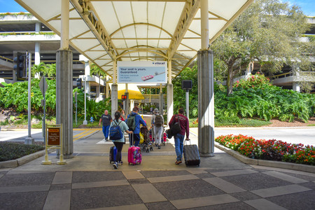 Orlando, Florida. March 01, 2019. People going to the parking lot with their luggage at Orlando International Airport. Editorial