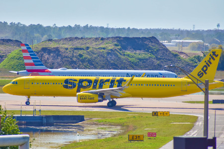 Orlando, Florida. March 01, 2019. Spirit Airlines and American Airlines aircraft on the runway preparing for departure from the Orlando International Airport (MCO).