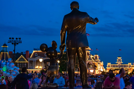 Orlando, Florida. April 03, 2019. Back view of Partners (Walt Disney and Mickey Mouse statues) on blue night background at Magic Kingdom.