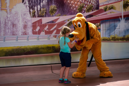 Orlando, Florida . March 27, 2019. Pluto playing with little girl at Epcot in Walt Disney World. (2) Redakční