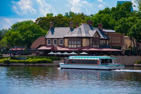 Orlando, Florida . March 27, 2019. Taxi boat sailing on blue lake in front of United Kingdom Pavilion at Epcot in Walt Disney World. Redakční