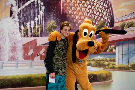 Orlando, Florida . March 27, 2019.Pluto hugging boy Epcot in Walt Disney World. Редакционное