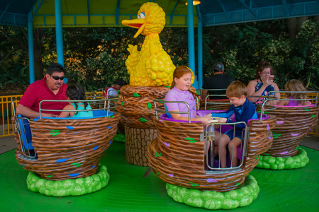 Orlando, Florida. April 7, 2019. Parent and Kids enjoying Big Birds Twirl N Whirl attraction at Seaworld in International Drive area (1)