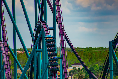 Orlando, Florida. April 7, 2019. People having fun amazin Mako rollercoaster on lightblue cloudy sky background at Seaworld in International Drive area (2) Фото со стока - 121383986