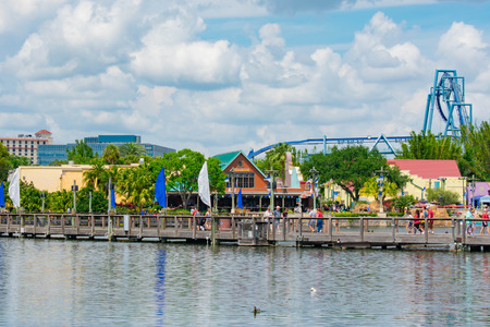 Orlando, Florida. April 7, 2019. People walking on wood bridge. View of colorful dockside and Manta Ray rollercoaster at Seaworld in International Drive area (1)